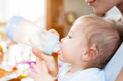 Baby boy food mother. A baby boy is fed with milk from a pacifier bottle by his young mother stock photography