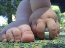Baby boy foot and hand over rubber floor Stock Images
