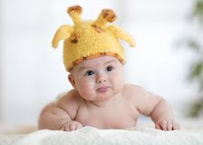 Baby boy in a funny giraffe hat lying on his belly in nursery. Newborn baby boy in funny giraffe hat lying on his belly in nursery Stock Image