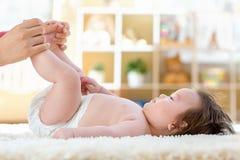 Baby boy getting a diaper change. Baby boy preparing for a diaper change stock photos
