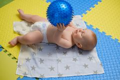Baby boy getting massage with special equipment. Baby boy getting a massage from masseuse royalty free stock image