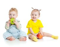 Baby boy and girl eating apples isolated stock images