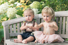 Baby boy and girl in formal dress sitting on wooden bench in a beautiful garden Stock Photos