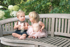 Baby boy and girl in formal dress sitting on wooden bench in a beautiful garden Stock Photography