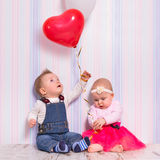 Baby boy and girl playing with hearts Stock Photography