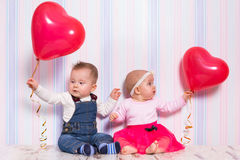 Baby boy and girl playing with hearts Stock Images