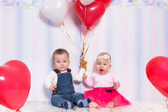 Baby boy and girl playing with hearts Stock Image