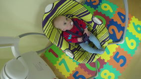 Baby boy or girl sway in colorful swing at home. 4K stock video