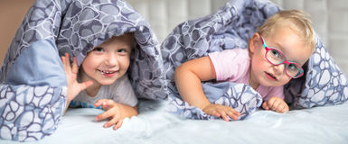 Baby boy and girl twins hiding in bed. Baby boy and girl twins hiding in parents bed Stock Photos