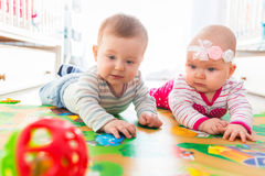 Baby boy and girl twins playing with the ball. At home royalty free stock photography