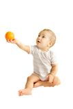 Baby boy giving an orange. Over white Royalty Free Stock Photo