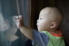 Baby boy at a  glass door Royalty Free Stock Photos