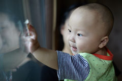 Baby boy at a  glass door Stock Photo