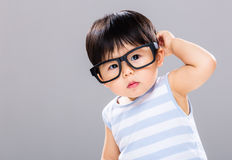 Baby boy with glasses and scratching his head Stock Image