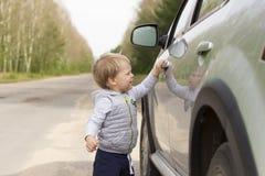 Baby boy going to open the car door. Baby boy going to open the car door Royalty Free Stock Image