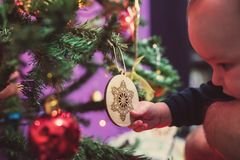 Baby boy grabbing an ornament form the Christmas tree Royalty Free Stock Images