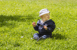 Baby boy on green grass. Cute one year old baby boy sat on green grass Royalty Free Stock Photo