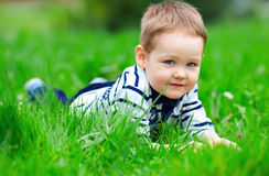 Baby boy on green grass outdoors Royalty Free Stock Photography