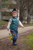 Baby boy in green jaket and blue jeans Stock Image