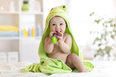 Baby with green towel after the bath biting toy royalty free stock photography