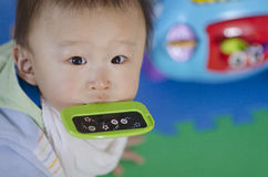Baby boy with a green toy in mouth. Close up, look at camera, on playing mat Royalty Free Stock Photos