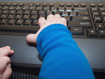 Baby boy hands on the computer keyboard Royalty Free Stock Photos