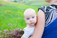Baby boy on hands of mother on meadow Stock Photos