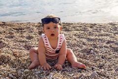 Baby boy in hat on beach pebbles Stock Photography