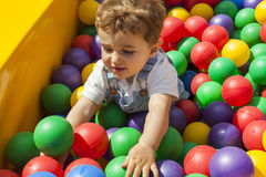 Baby boy having fun playing in a colorful plastic ball pool Stock Photos