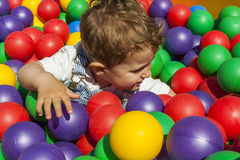Baby boy having fun playing in a colorful plastic ball pool Stock Photo