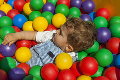 Baby boy having fun playing in a colorful plastic ball pool Stock Images