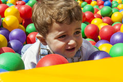 Baby boy having fun playing in a colorful plastic ball pool Royalty Free Stock Image
