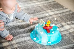 Baby boy having his nine month birthday. And big cake Stock Photography