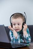 Baby boy with headphones. At the computer Stock Photo