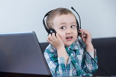 Baby boy with headphones at the computer. Looking interested over the top of it and smiling Royalty Free Stock Photos
