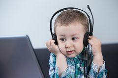 Baby boy with headphones at the computer. Toddler using headphones while looking at the laptop's screen Royalty Free Stock Photography