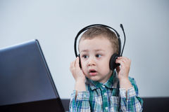 Baby boy with headphones. Watching carefully at the computer Stock Photos