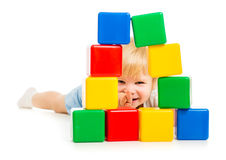 Baby boy hidden behind building blocks. Isolated stock photography
