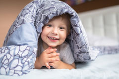 Baby boy hiding in bed. Baby boy hiding in parents bed Stock Image