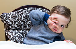 Baby Boy in High Chair Hiding Behind his Hand.  Stock Images