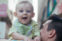 Baby Boy In His Father's Embrace Walking Through City Stock Photo