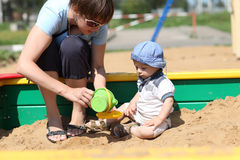 Baby boy and his mother in sandbox. Baby boy and his mother are playing in sandbox in summer Royalty Free Stock Photo