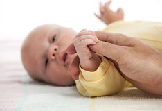 Baby boy holding father's hand Stock Photo