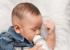 Baby boy holding milk bottle Royalty Free Stock Photos