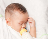 Baby boy holding milk bottle Stock Image