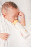 Baby boy holding milk bottle Stock Photography