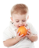 Baby boy holding an orange Stock Images
