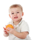 Baby boy holding an orange Stock Photography