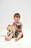 Baby boy holding a Pug. Baby boy with his new pet Pug, getting to know each other royalty free stock image