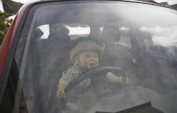 Baby Boy Holding Steering Wheel In Car. Happy baby boy holding steering wheel in car Royalty Free Stock Image